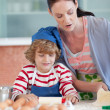 Smiling mother baking at ome with her son - Stock Photo