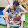 Father and son playing in a tent - Stock Photo