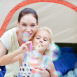 Mother and daughter together in tent — Stock Photo