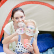 Mother and daughter blowing bubbles — Stock Photo