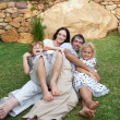 Smiling family resting in a garden — Stock Photo #10312073