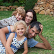 Smiling family resting in a garden — Stock Photo