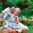Young mother and daughter watering plants — Stock Photo