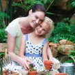 Young mother and daughter watering plants — Stock Photo #10312089