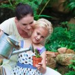 Young mother and daughter watering plants — Stock Photo #10312094