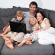Smiling family using a laptop on a sofa - Stockfoto