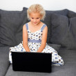 Stock Photo: Young girl using laptop on sofa