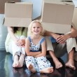 Parents and daughter playing at home with boxes — Stock Photo #10312248