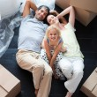 Parents and daughter on the floor with a lot of boxes - Stockfoto