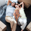 Parents and daughter on the floor with a lot of boxes - Photo