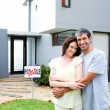 Newlyweds with their new house - Stockfoto