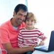 Royalty-Free Stock Photo: Father and son playing with a laptop