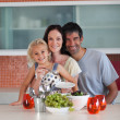Smiling family eating in a kitchen — Stock Photo
