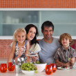 Happy family eating in a kitchen — Stock Photo #10312338
