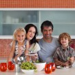 Happy family eating in a kitchen — Stock Photo