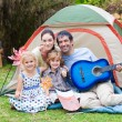 Family playing a guitar in a tent — Stock Photo