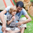Dad and son blowing bubbles - Stockfoto