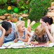 Happy family drawing in a park - 