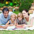 Happy family painting in a park smiling at the camera - Stockfoto
