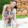 Stock Photo: Mother and son drawing in a park