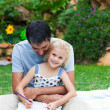 Royalty-Free Stock Photo: Father and daughter reading in a park
