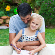 Stock Photo: Father and daughter drawing in a park