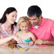 Parents helping their daughter doing homework — ストック写真