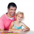 Daughter and father drawing looking at the camera — Stock Photo
