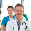 Foto Stock: Mature doctor leading his team with copy-space