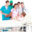 Doctors attending to a mother and her newborn baby — Stock Photo