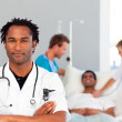 Serious doctor with folded arms and patient in the background — Stock Photo #10313238