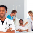 Portrait of an African doctor with a patient in the background — Stock Photo #10313243