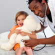 Children's doctor exams a little girl with stethoscope — Stock Photo #10313275
