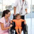 Doctors with a little girl sitting on a wheelchair — Stock Photo #10313283