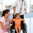 Doctors with a little girl sitting on a wheelchair — Stock Photo