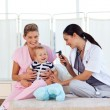 Baby playing with pediatrician and nurse — Stock Photo
