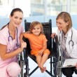 Little girl in a wheelchair with nurse and doctor — Stock Photo