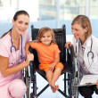 Little girl in a wheelchair with nurse and doctor — Stock Photo #10313321