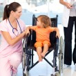 Young nurse talking to a baby in a wheelchair — Stock Photo #10313347