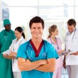 Attractive doctor with is team in the background — Stock Photo #10313449