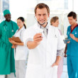 Stock Photo: Young doctor with stethoscope and his team