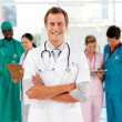 Young and smiling doctor with his team in the background — Stock Photo