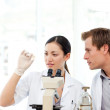 Scientists looking at a slide under a microscope — Stock Photo #10313542