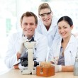 Young scientists working with a microscope — Stock Photo #10313560