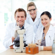 Young scientists working with a microscope — Stock Photo