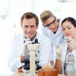 Scientists looking at a slide under a microscope — Stock Photo