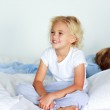 Little girl in bed smiling while her brother is sleeping — Stock Photo #10313583