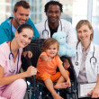 Baby girl in a wheelchair with medical team — Stock Photo #10313609