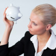 Sad Business woman looking into Piggy Bank - Stockfoto