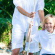 Mother and son swinging in a park — Stock Photo